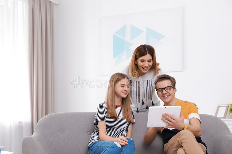 Happy mother, her teenager daughter and son with tablet stock images