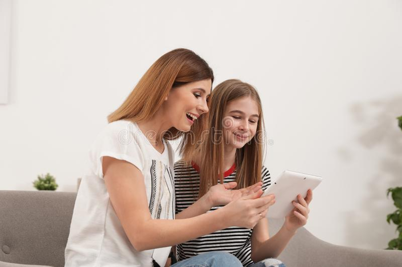 Happy mother and her teenager daughter with tablet computer royalty free stock image