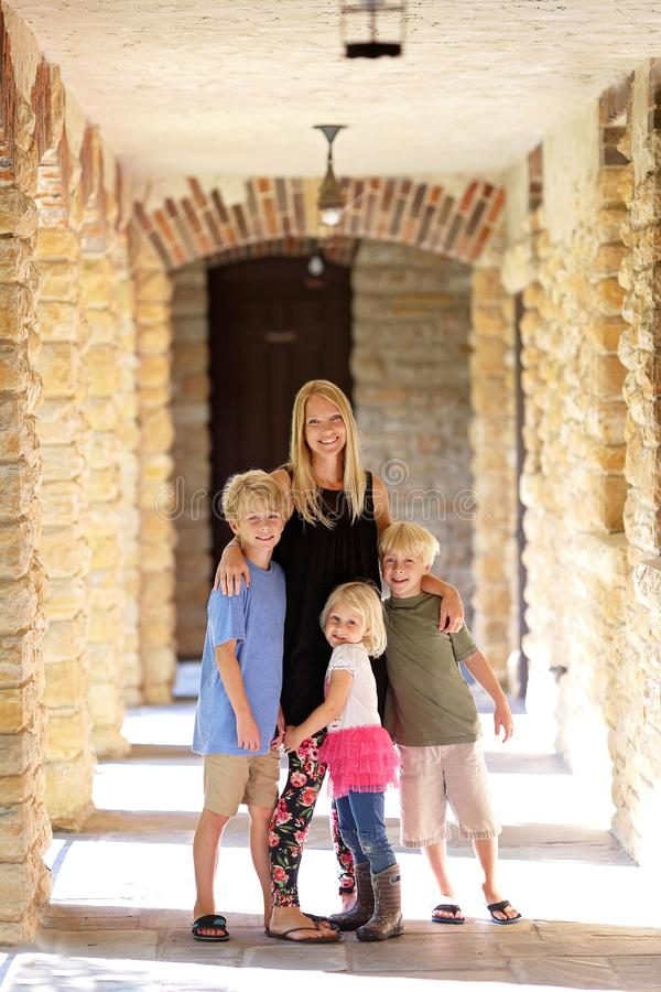 Happy Mother and her Young Children Visiting Old Historic Stone Building stock image