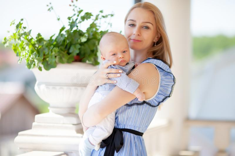 Happy mother holding a baby in her arms, family portrait of mum and child stock photo