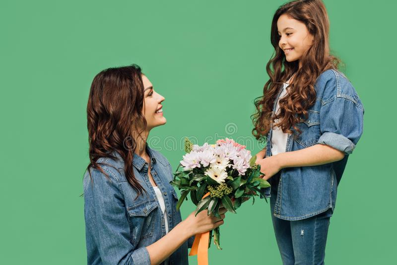 Happy mother holding flowers presented from adorable smiling daughter isolated royalty free stock image