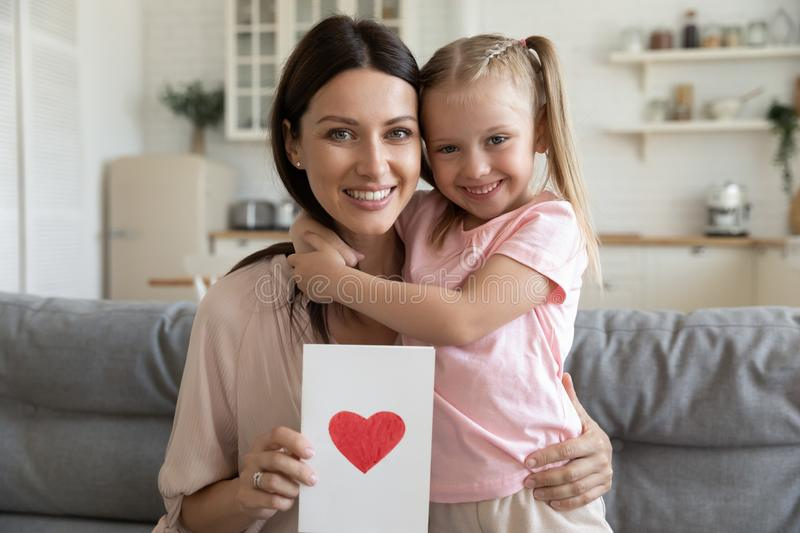 Happy mother holding postcard with drawn red heart embraces daughter. Happy beautiful women holding postcard with drawn red heart embraces little daughter people stock photo