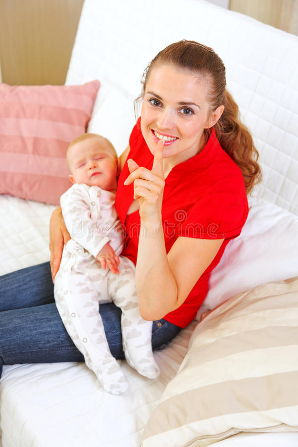 Happy mother holding sleeping baby and showing shh. H gesture stock photo