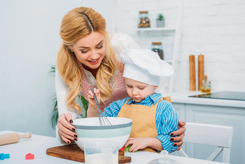 Happy mother holding son while he using hand royalty free stock photos
