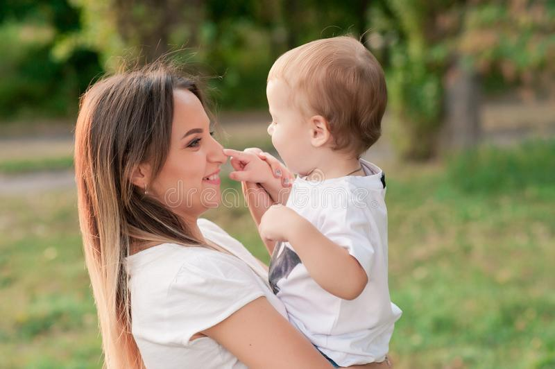 Happy mother holds cute smiling son in the park stock photography