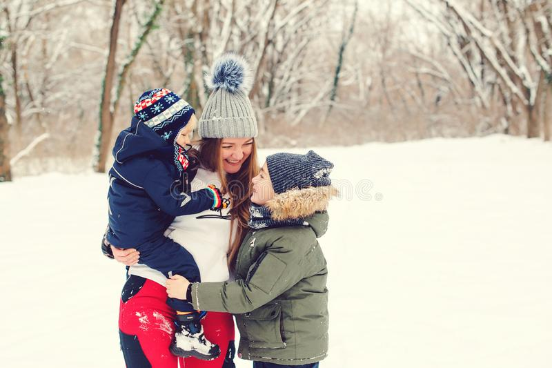 Happy mother hugging her cute sons, smiling and laughing. Winter fashion. Christmas and winter holidays. Happy kids with mom on a. Winter walk royalty free stock photo
