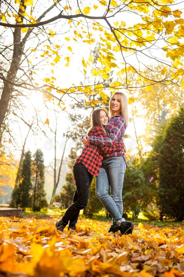Happy mother hugging her teenage daughter posing in the sunlight royalty free stock image