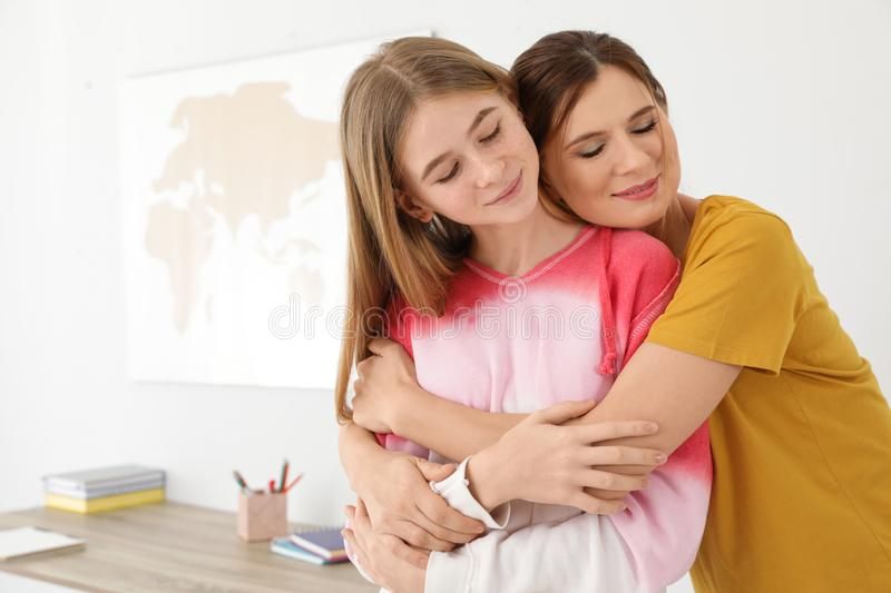 Happy mother hugging her teenager daughter. At home royalty free stock photo