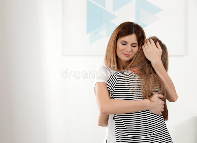 Happy mother hugging her teenager daughter stock photo