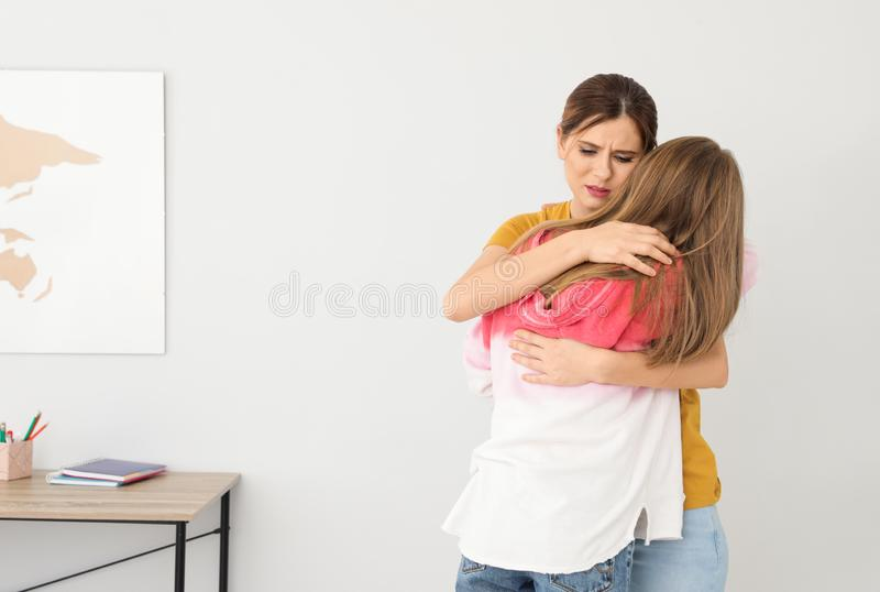 Happy mother hugging her teenager daughter. At home royalty free stock photography