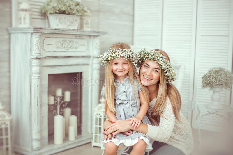 A happy mother is hugging tight her young daughter royalty free stock image