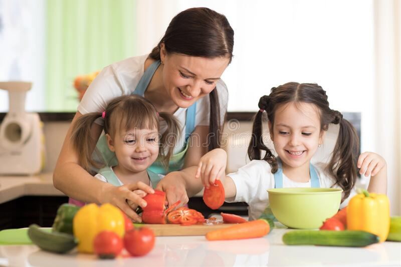 Happy mother and kids cooking and cutting vegetables on kitchen royalty free stock photos