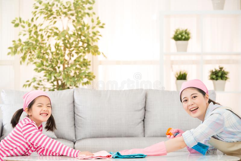 Happy mother with kids spring cleaning. Room and having fun playing at home. A young women and a little child girl dusting. family housework and household stock image