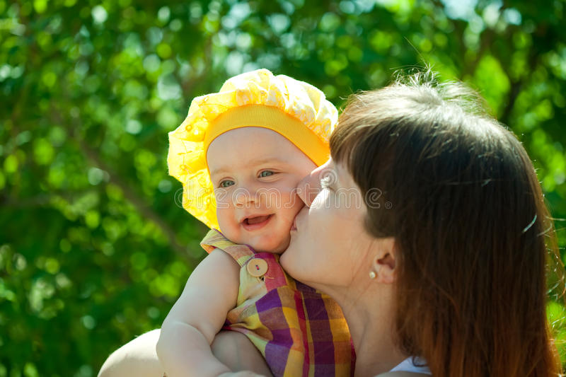 Happy mother kissing baby stock images