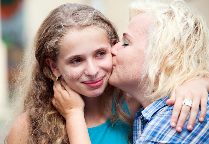 Happy mother kissing her daughter stock images