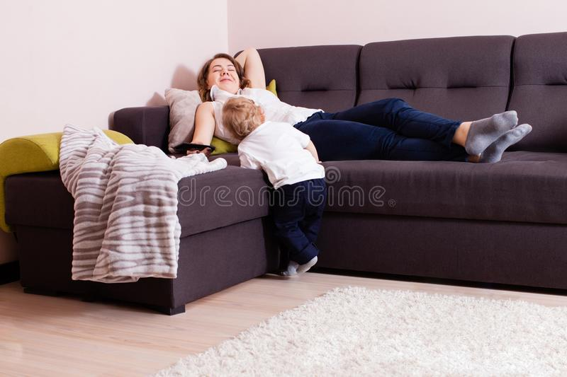 Happy mother laying on sofa with her baby boy standing near her stock image