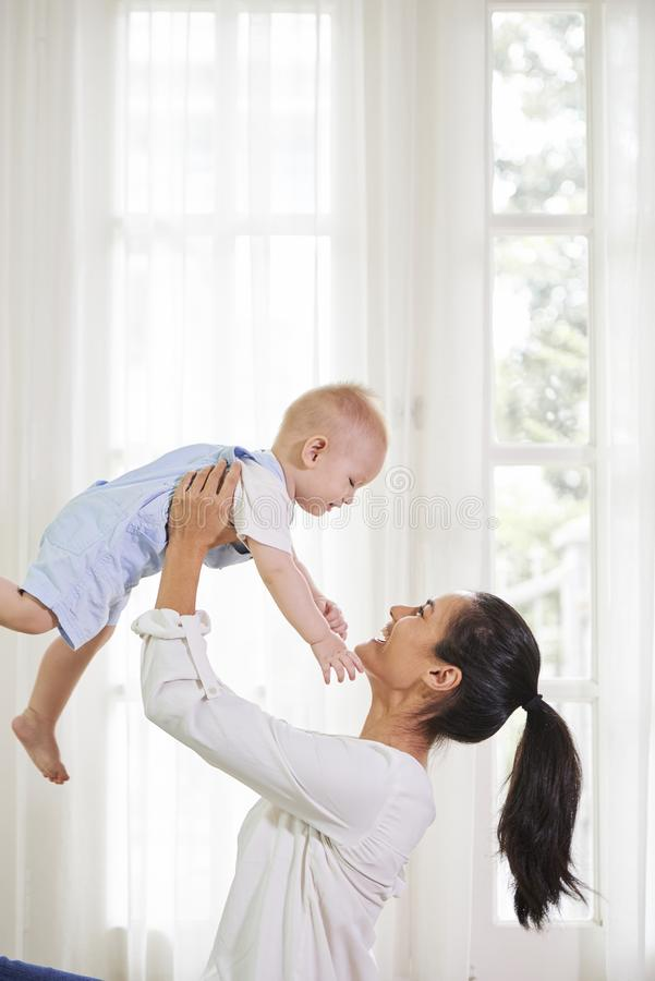 Happy mother lifting baby royalty free stock photos
