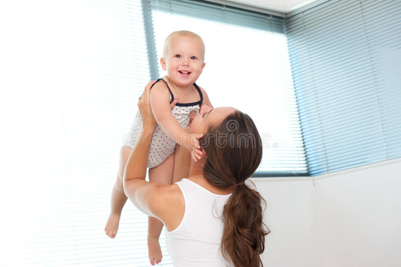 Download Happy Mother Lifting Up Cute Baby At Home Stock Image - Image: 34073557