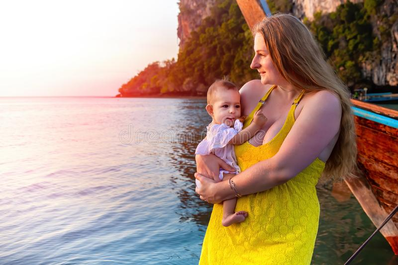 Happy mother with a little baby stand on the pier against the background of water in the early morning and meet sunrise. Enjoy the. Moment stock images