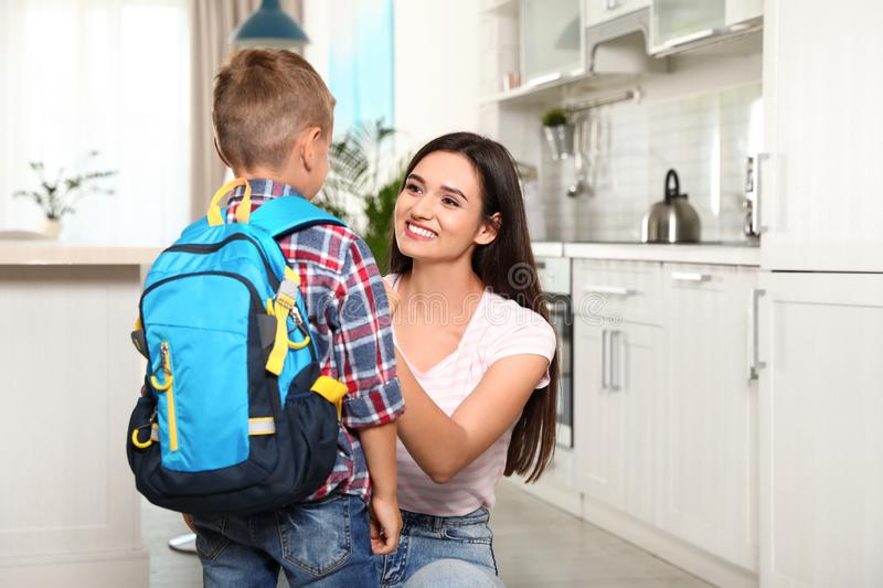Happy mother and little child with backpack ready for school stock images