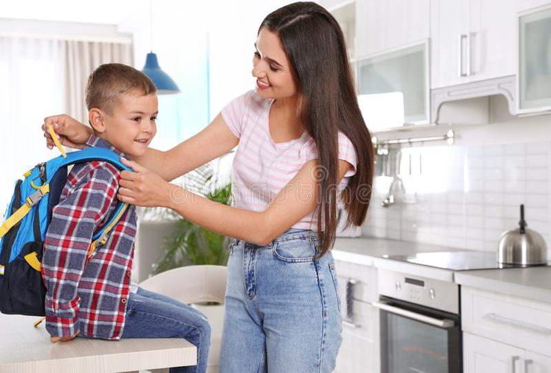 Happy mother and little child with backpack ready for school. In kitchen royalty free stock photography
