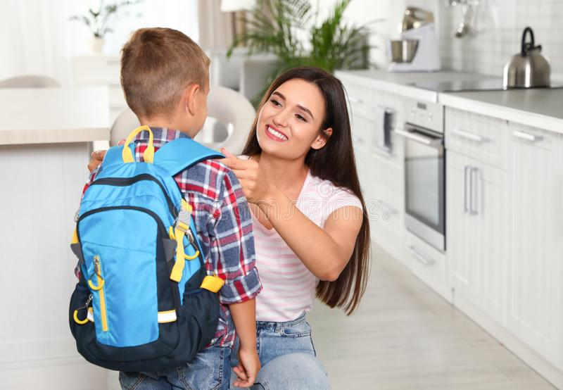 Happy mother and little child with backpack ready for school. In kitchen stock image