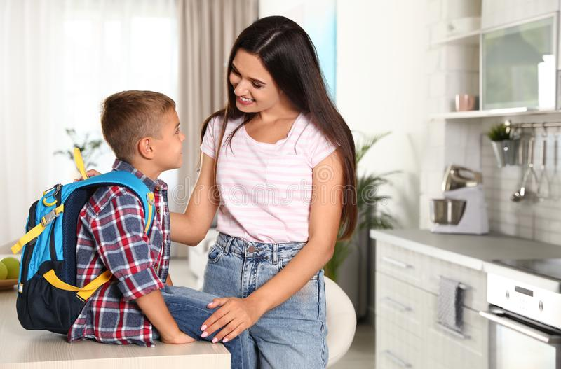Happy mother and little child with backpack ready for school stock photo