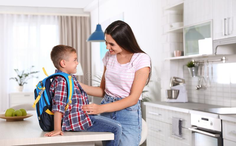 Happy mother and little child with backpack ready for school. In kitchen royalty free stock images