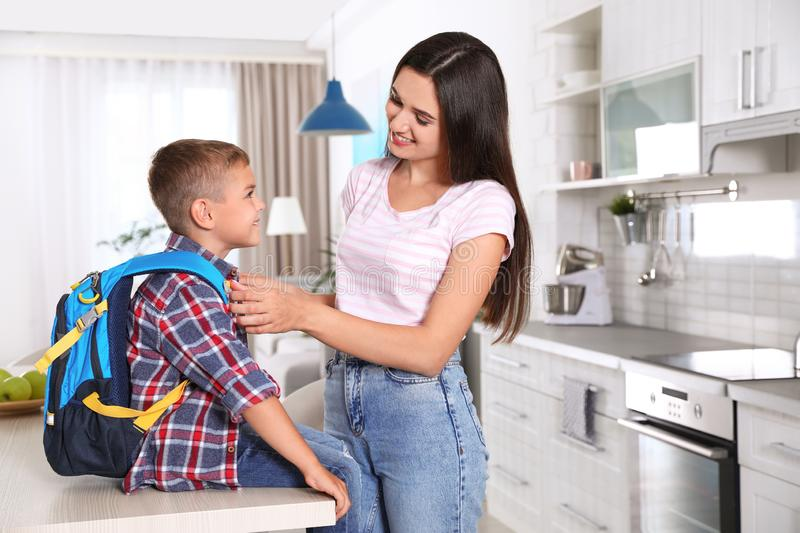 Happy mother and little child with backpack ready for school stock photos