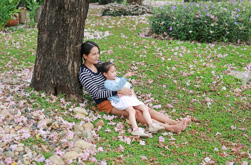 Happy mother and little child girl lying on green grass with fall pink flower in the garden outdoor. Asian girl pointing for her stock image