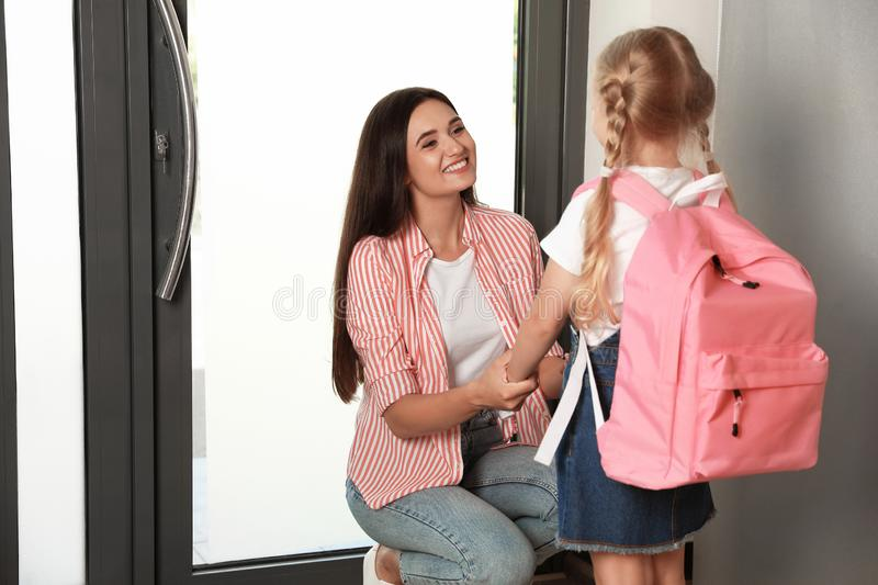 Happy mother and little child with school bag. At door stock photos