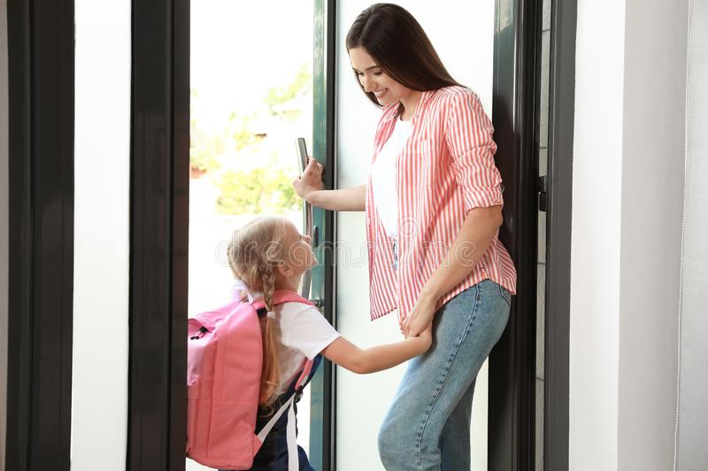 Happy mother and little child with school bag. In doorway stock image