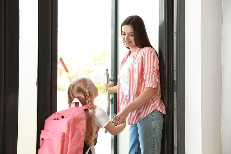 Happy mother and little child with school bag. In doorway royalty free stock image