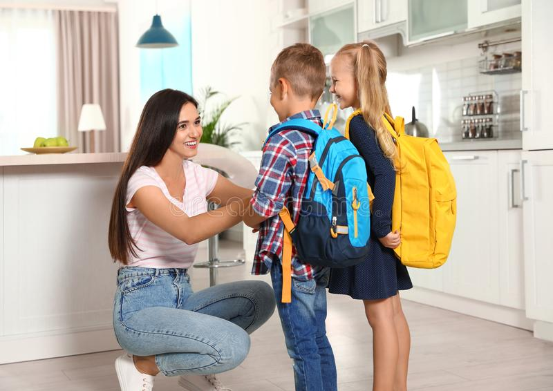 Happy mother and little children with school bags stock photography