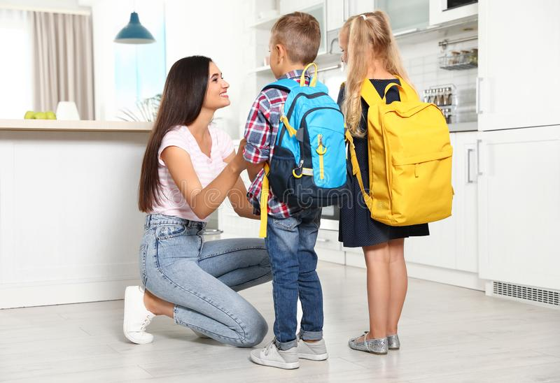 Happy mother and little children with school bags royalty free stock photos