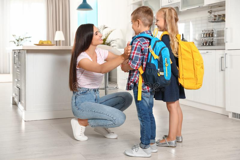 Happy mother and little children with school bags. In kitchen stock photo