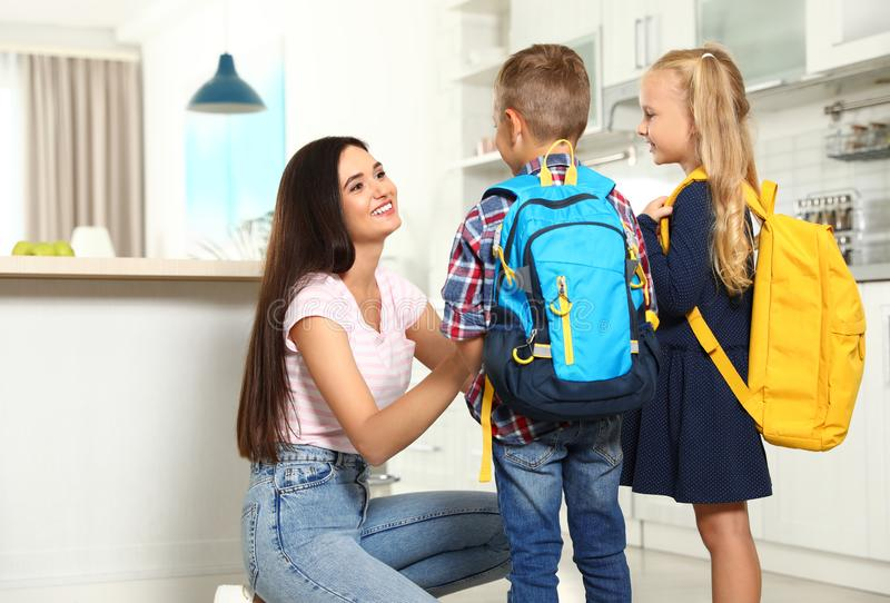 Happy mother and little children with school bags. In kitchen royalty free stock photos