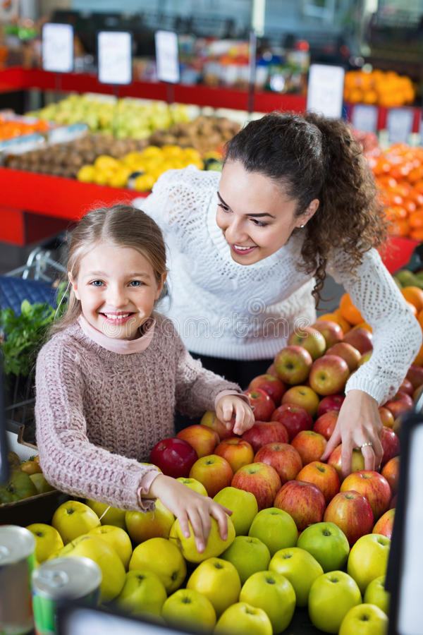 Happy mother and little daughter choosing seasonal fruits. Happy smiling mother and little daughter choosing seasonal fruits in grocery stock image