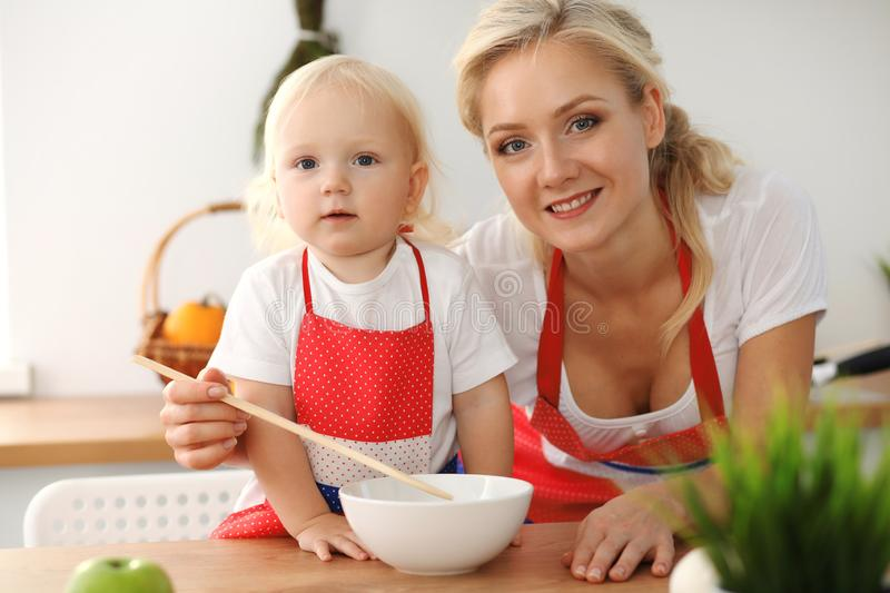 Happy mother and little daughter cooking in kitchen. Spending time all together, family fun concept stock photos