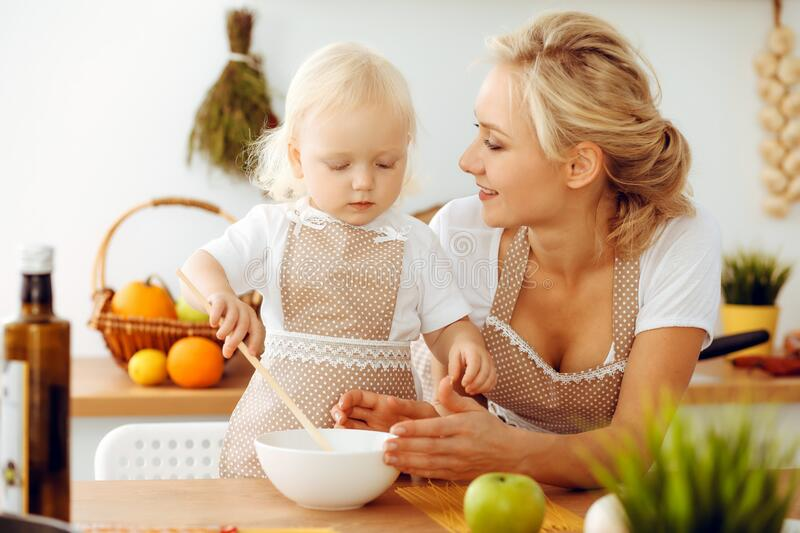 Happy mother and little daughter cooking in kitchen. Spending time all together, family fun concept royalty free stock photos