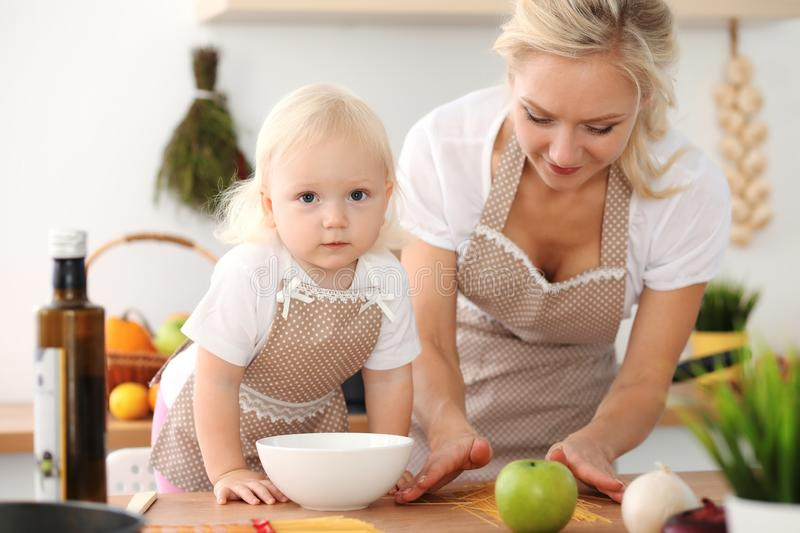 Happy mother and little daughter cooking in kitchen. Spending time all together, family fun concept stock photography
