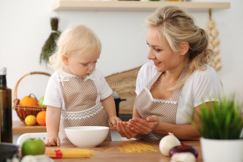 Happy mother and little daughter cooking in kitchen. Spending time all together, family fun concept royalty free stock photography