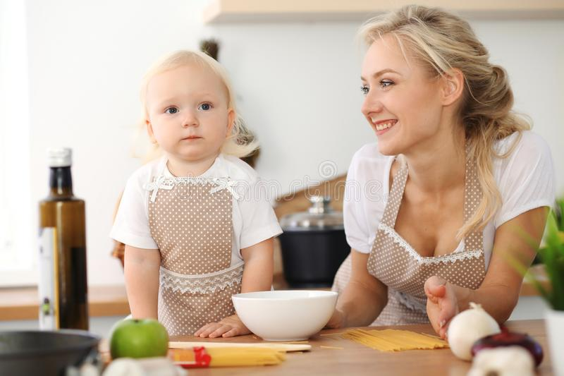 Happy mother and little daughter cooking in kitchen. Spending time all together, family fun concept royalty free stock photo
