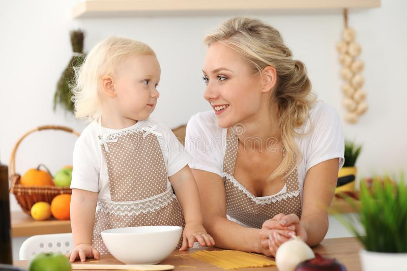 Happy mother and little daughter cooking in kitchen. Spending time all together, family fun concept stock images