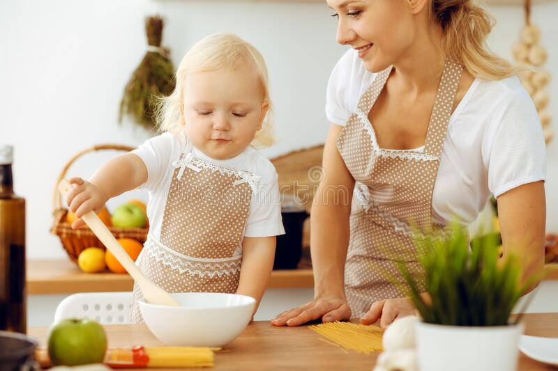 Happy mother and little daughter cooking in kitchen. Spending time all together, family fun concept royalty free stock image