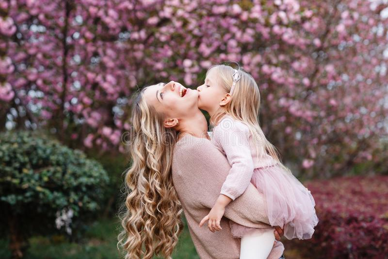Happy mother and little daughter with long blonde hair embracing in the park. Family concept. Springtime, blooming trees royalty free stock photo