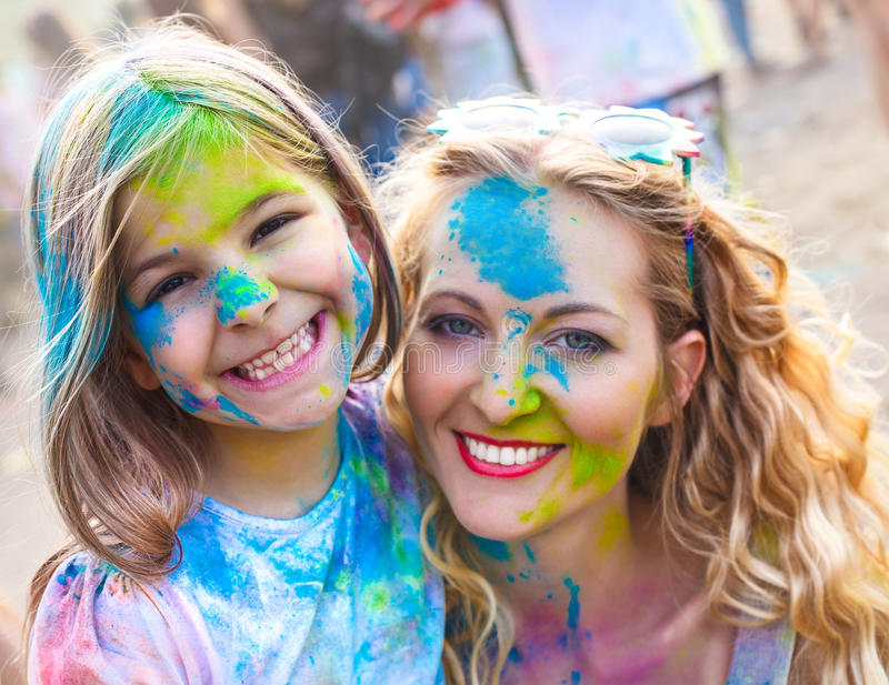 Happy mother with little daughter on holi festival royalty free stock images