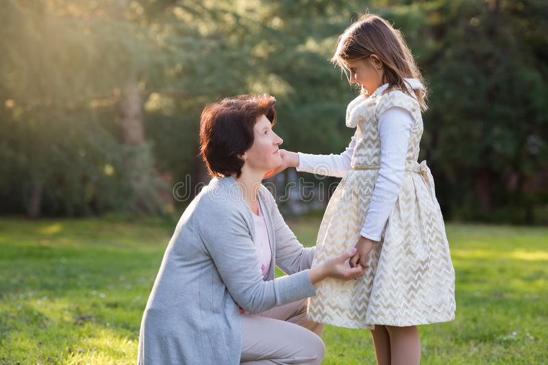 Happy mother and little daughter looking at each other, little girl holding mother`s cheek, mother`s day concept royalty free stock image