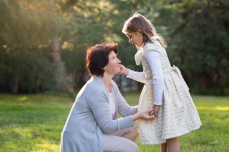 Happy mother and little daughter looking at each other, little girl holding mother`s cheek, mother`s day concept stock image