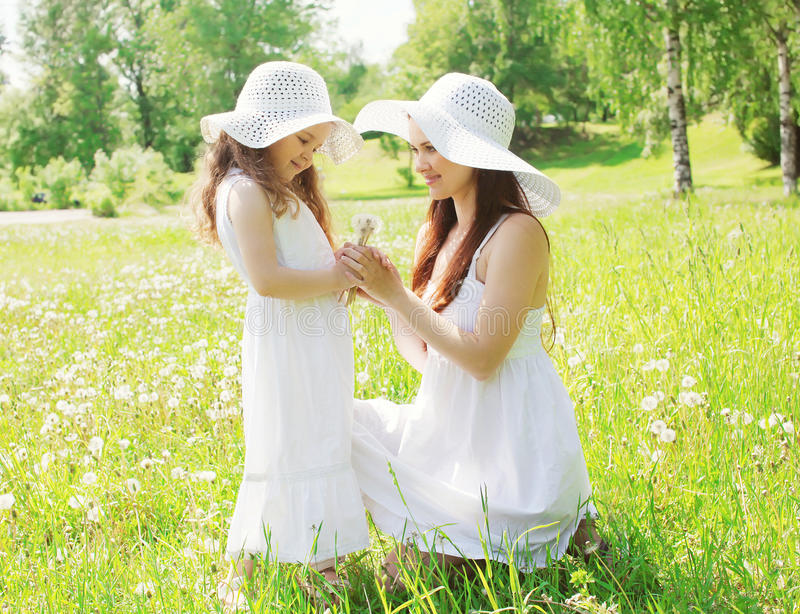 Happy mother and little girl child wearing a straw hat with dandelions. Flowers in spring field royalty free stock image